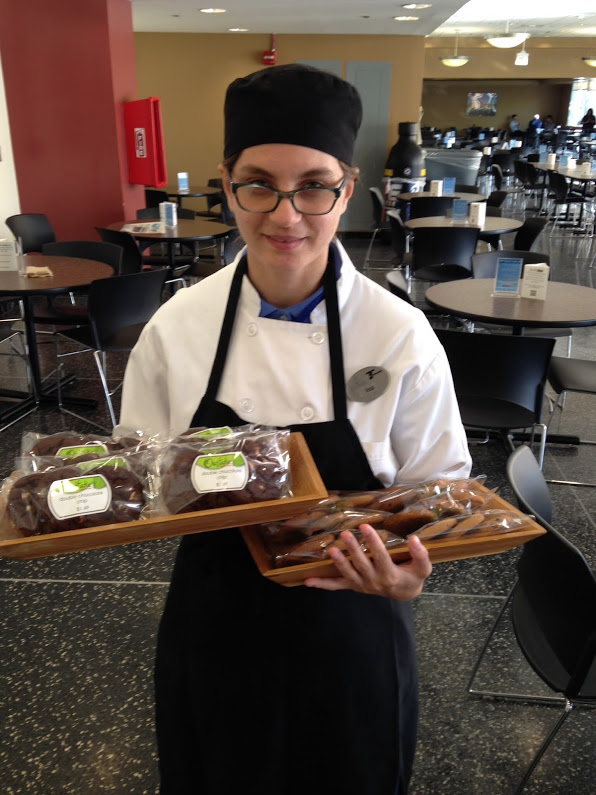 Person in a cooking apron holding a trays of cookies in a cafeteria.